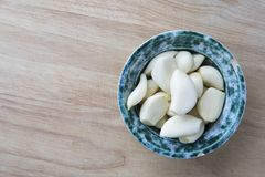 Peeled Garlic Coves in Bowl. Peeled garlic cloves in bowl on cutting board viewed from directly above Stock Photography