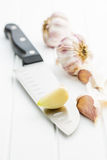Peeled garlic on knife. The peeled garlic on knife Stock Photography