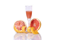 Peeled grapefruit and juice. Isolated peeled grapefuit and glass and juice on mirror-like surfase Stock Photography
