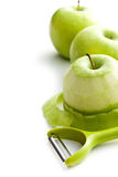 Peeled green apple with peeler Royalty Free Stock Photos