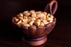 Peeled grillade jordnötter i keramisk bunke på trätabellen royaltyfri bild