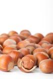 Peeled hazelnut among unpeeled, isolated on white Royalty Free Stock Images