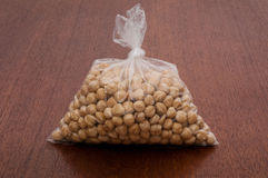 Peeled hazelnuts. Closed plastic bag with peeled hazelnuts on brown wooden table Stock Image