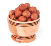 Peeled hazelnuts in a wooden bowl on  white background Royalty Free Stock Photo
