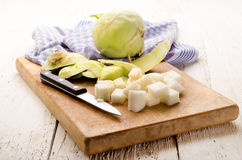 Peeled kohlrabi and kitchen knife on a wooden board Stock Photos