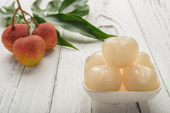 Peeled lichee in front with some fresh unpeel ones. On back Stock Photo