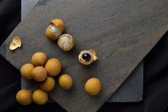 A peeled longan (dimocarpus longan) with a bunch of ripe longan Royalty Free Stock Image