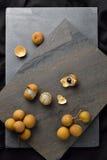 A peeled longan (dimocarpus longan) with a bunch of ripe longan Royalty Free Stock Photo