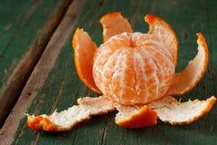 Peeled mandarin on green board Royalty Free Stock Photos