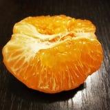 Peeled mandarin orange on black Stock Images