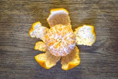 Peeled mandarin on the peel in the form of a flower on an old oak board. stock photo
