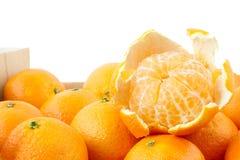 Peeled mandarin on top of crate Stock Photos