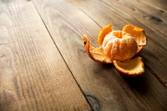 Peeled mandarin on a wooden bacground. A peeled mandarin on a wooden bacground Royalty Free Stock Photo