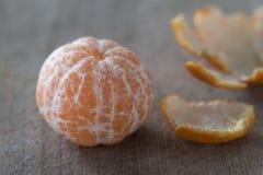Peeled mandarine fruit on wooden board. Peeled fresh mandarine fruit on wooden board royalty free stock photo