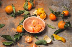 Peeled mandarins in a bowl with bamboo, green leaves Royalty Free Stock Images
