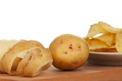 Peeled potato. Peeled new potato with crispy chips on white background close-up Stock Photo