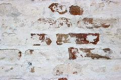 Peeled off with time, white painted brickwork stock image