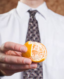 Peeled Orange. Closeup view of a businessman holding an orange that is partially peeled Stock Photography