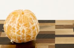 Peeled Orange on a Cutting board. Against a white background royalty free stock images