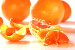 Peeled orange and whole oranges Royalty Free Stock Image