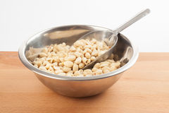 Peeled peanuts in bowl with transfer scoop Stock Photo