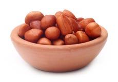 Peeled peanuts on a clay pot Royalty Free Stock Photos