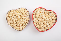 Peeled peanuts  in heart shape box Stock Photos