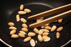 Peeled peanuts roasted in a black pan as a snack or to cook Asia Royalty Free Stock Image