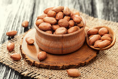 Peeled peanuts in a wooden bowl on an old burlap Stock Image