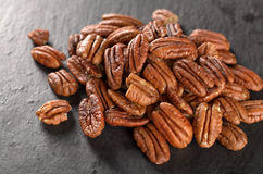 Peeled pecan nuts on a slate plate, selective focus. Tasty peeled pecan nuts on a black slate plate, selective focus Royalty Free Stock Photo
