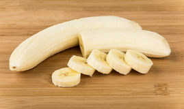 Peeled from peel of ripe banana and pieces on board Stock Photography