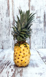 Peeled pineapple. Surrounded by rustic background Royalty Free Stock Photos