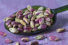 Peeled pistachio nuts in a spoon, isolated, purple wooden background Royalty Free Stock Images