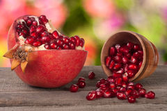 Peeled pomegranate and garnet grains in a bowl on wooden background Royalty Free Stock Images