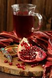 Peeled pomegranate, glass of pomegranate juice and jewerly on wo. Oden board with wood background Stock Image