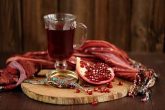 Peeled pomegranate, glass of pomegranate juice and jewerly on wo. Oden board with wood background Stock Photo