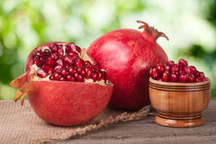Peeled pomegranate and whole with garnet grains in a bowl on wooden background Stock Photography