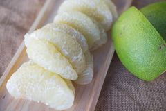 The peeled pomelo. The fresh peeled pomelo on wooden tray Royalty Free Stock Image