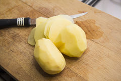 Peeled potato on a cutting board Royalty Free Stock Photography