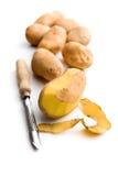 Peeled potato with old potato peeler Stock Photo