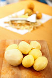 Peeled potatoes. On wooden plate on the table, in the background a peeler and potatoes - vertical Stock Image