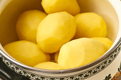 Peeled potatoes in bowl Stock Image