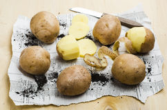 Peeled potatoes with the peel and knife. On a wooden table Stock Photo