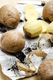 Peeled potatoes with the peel and knife. On a wooden table Stock Images