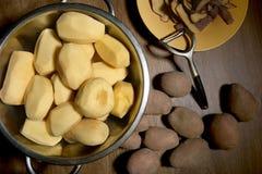 Peeled potatoes with peeler. Stock Image