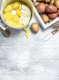 Peeled potatoes in a pot and raw potatoes on the tray royalty free stock photos