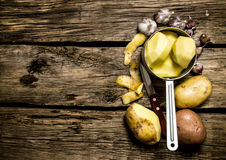 The peeled potatoes in a saucepan with garlic and knife on wooden background . Free space for text. Royalty Free Stock Images