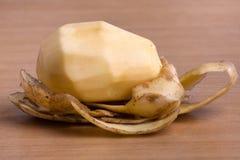 Peeled potatoes on wooden background Stock Photo