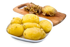 Peeled potatoes with wooden board in  background Royalty Free Stock Photos