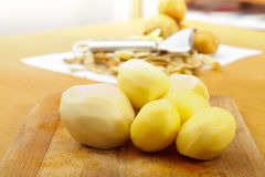 Peeled potatoes on wooden plate Stock Photo